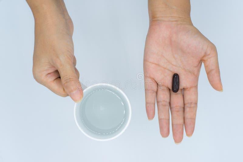 Mãos fêmeas que guardam o copo de água e da cápsula preta imagem de stock royalty free