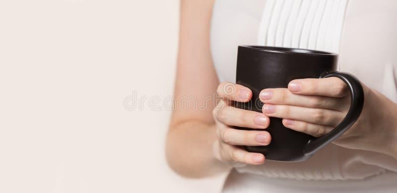 Mãos fêmeas que guardam o copo de café escuro imagem de stock