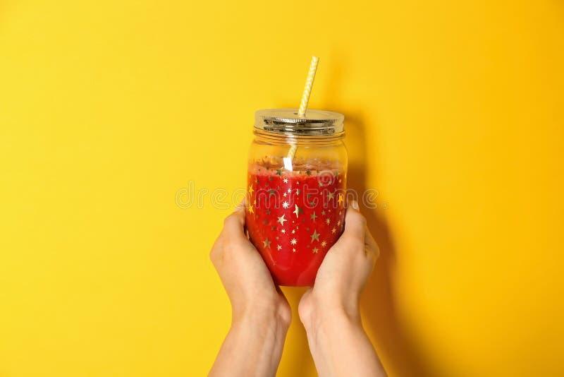 Mãos fêmeas que guardam o frasco de pedreiro com o batido saboroso no fundo da cor fotografia de stock royalty free