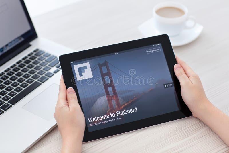 Mãos fêmeas que guardam o iPad com app Flipboard na tela no th imagens de stock royalty free