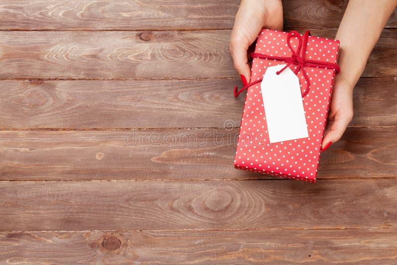 Mãos fêmeas que guardam o presente acima da tabela de madeira imagens de stock royalty free