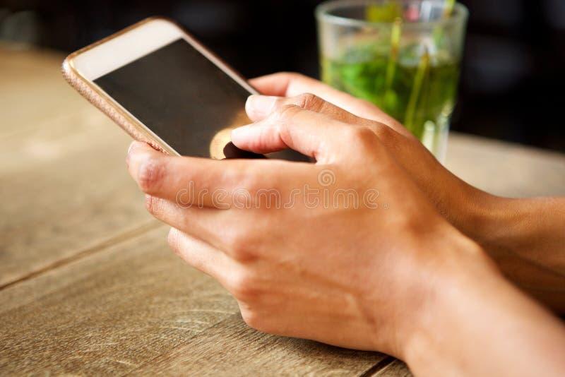 Mãos fêmeas que guardam o telefone celular na tabela com bebida fotos de stock