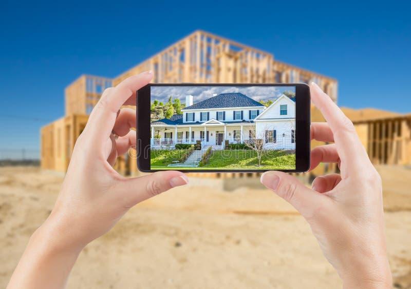 Mãos fêmeas que guardam o telefone esperto que indica a foto da casa com foto de stock