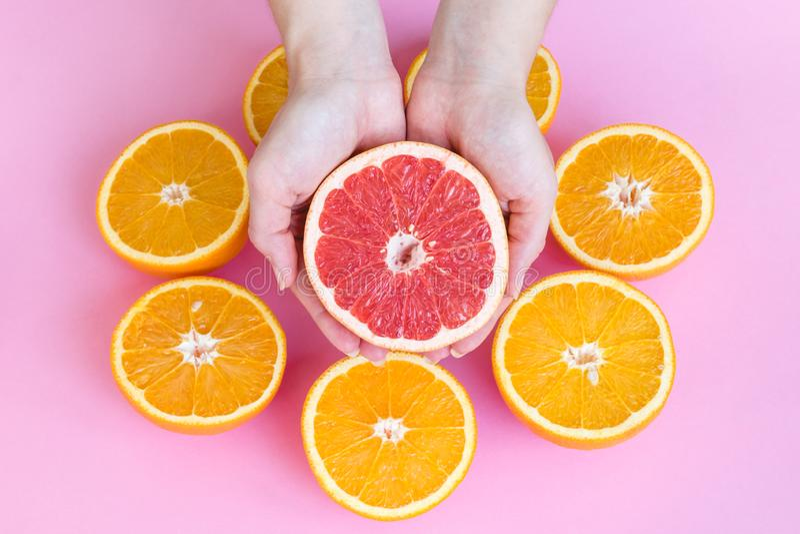 Mãos fêmeas que guardam parcialmente de uma toranja vermelha madura suculenta acima das laranjas cortadas ao meio em um fundo cor foto de stock royalty free