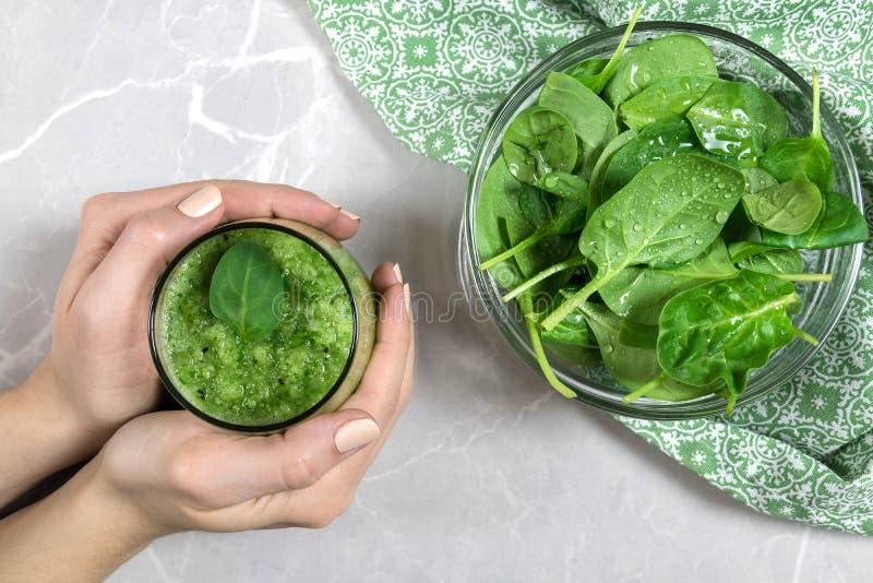 Mãos fêmeas que guardam um batido verde fresco dos espinafres e do quivi imagem de stock royalty free