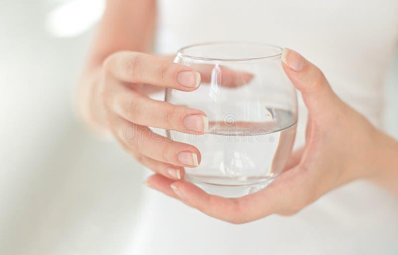 Mãos fêmeas que guardam um vidro claro da água Um vidro da água mineral limpa nas mãos, bebida saudável foto de stock