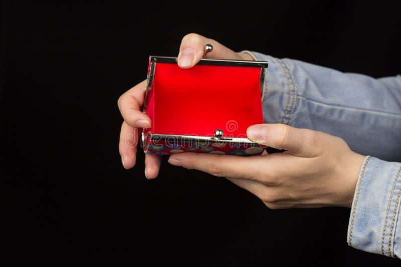 Mãos fêmeas que guardam uma bolsa vermelha vazia em um fundo preto, close-up fotografia de stock