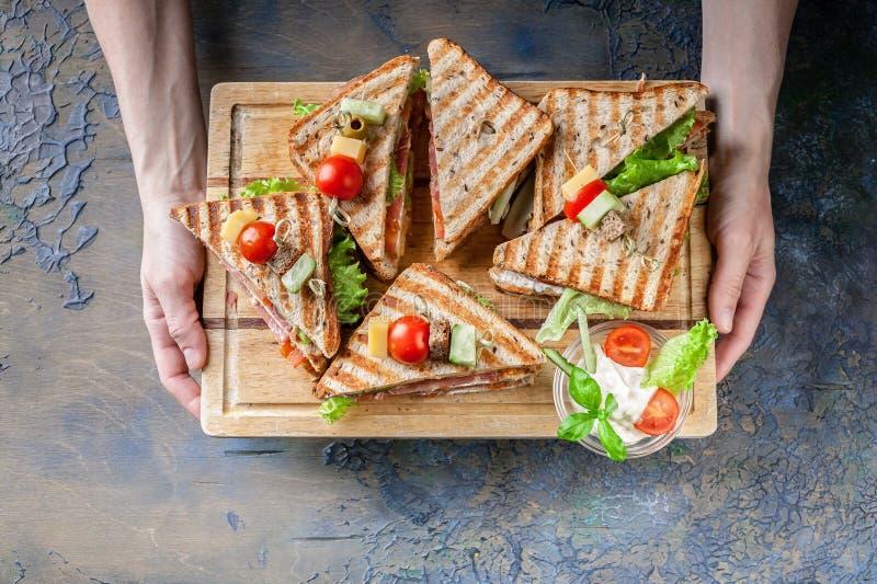 M?os f?meas que guardam uma placa de madeira com os sandu?ches frescos da carne, os tomates e salada verde Caf? da manh?, almo?o  imagem de stock