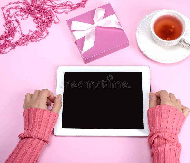 Mãos fêmeas que guardam uma tabuleta eletrônica com um sc vazio do preto fotos de stock