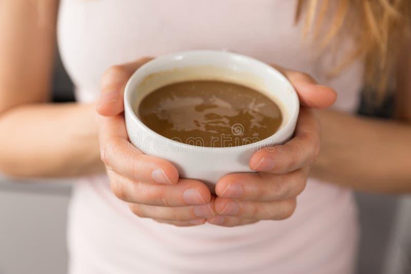 Mãos fêmeas que guardam uma xícara de café fotografia de stock