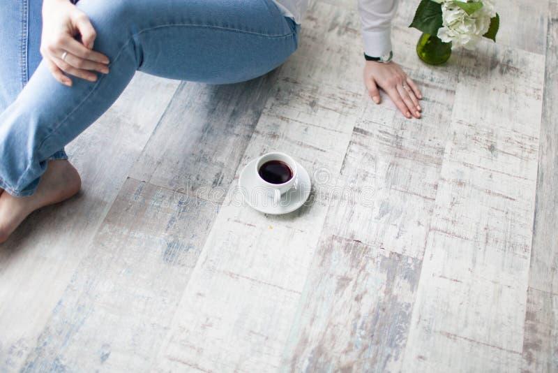 Mãos fêmeas que guardam xícaras de café no fundo de madeira rústico imagem de stock royalty free