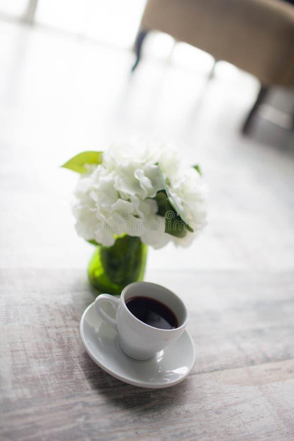 Mãos fêmeas que guardam xícaras de café no fundo de madeira rústico fotos de stock royalty free