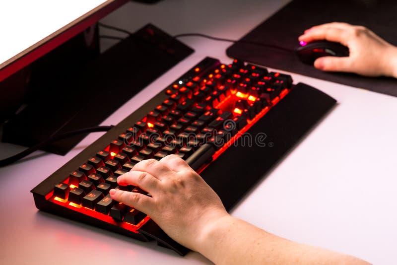 Mãos fêmeas que jogam o jogo de computador com engrenagem do jogo imagem de stock royalty free