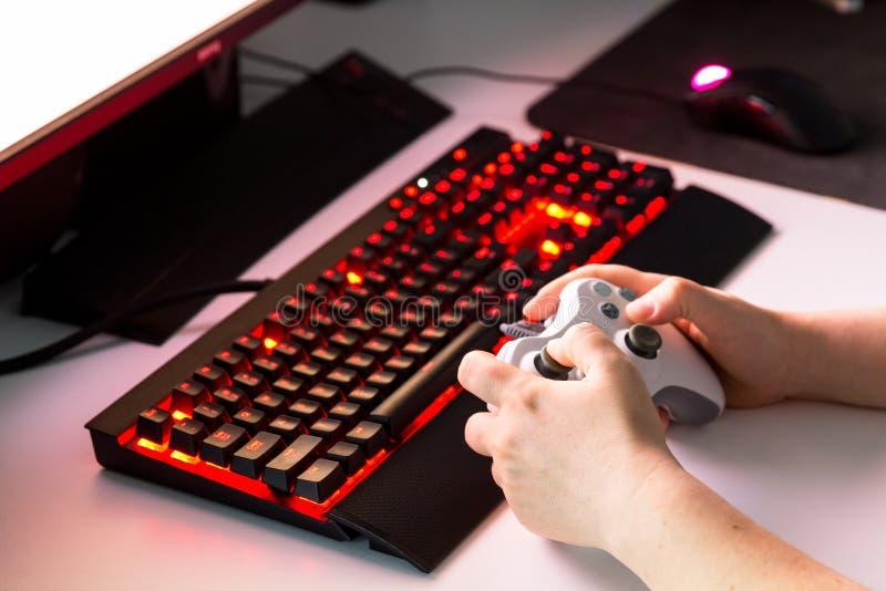 Mãos fêmeas que jogam o jogo de computador com engrenagem do jogo imagens de stock