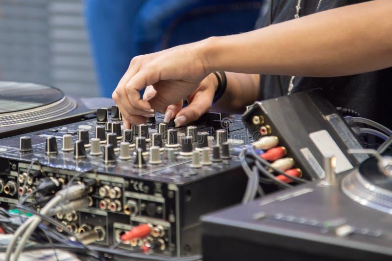 Mãos fêmeas que jogam o misturador do DJ foto de stock royalty free