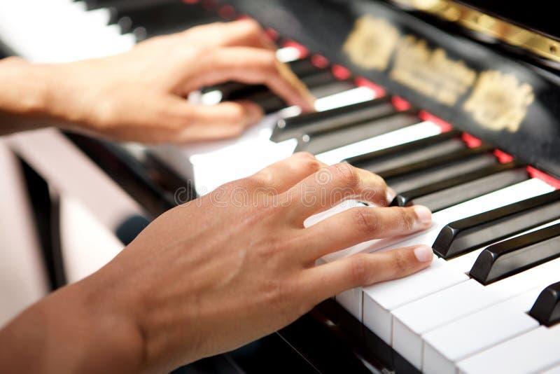 Mãos fêmeas que jogam o piano imagens de stock