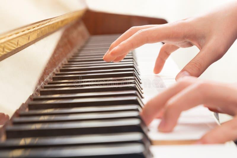 Mãos fêmeas que jogam o piano fotografia de stock