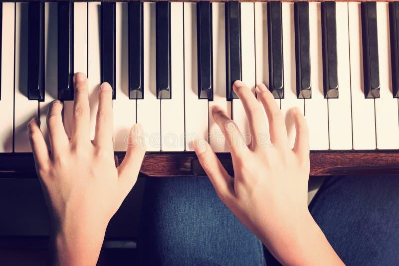 Mãos fêmeas que jogam o piano com olhar do vintage fotografia de stock royalty free