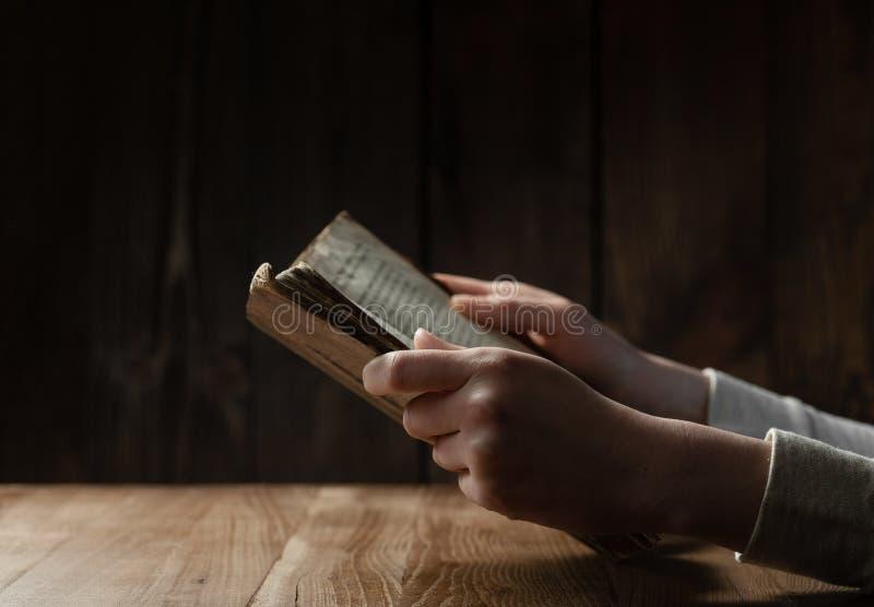 Mãos fêmeas que leem o livro velho imagem de stock royalty free