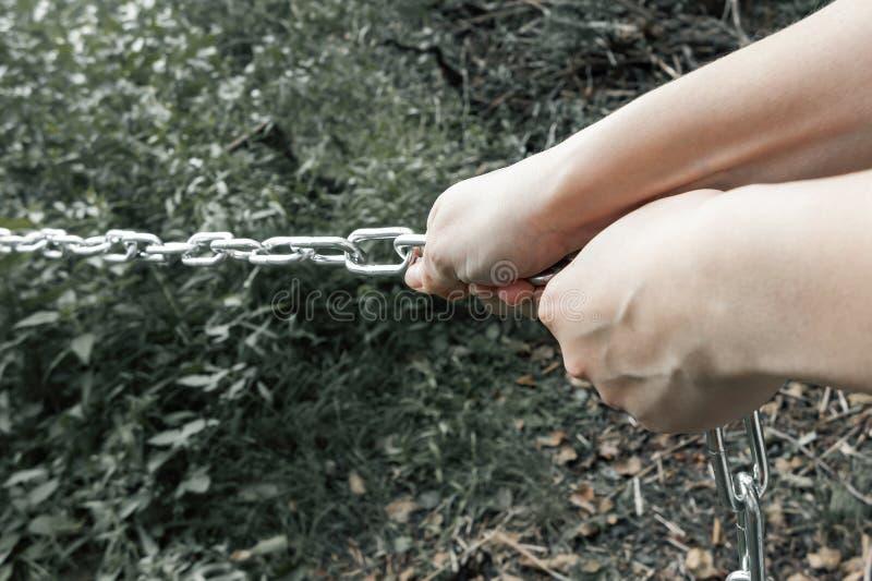 Mãos fêmeas que puxam uma corrente grossa do metal - o conceito do trabalho duro, carga insuportável fotografia de stock