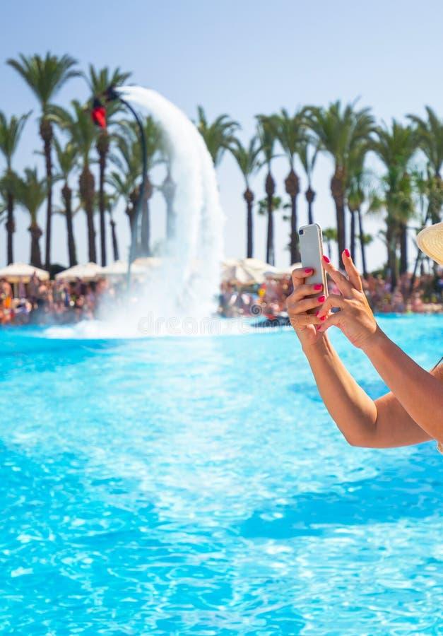 Mãos fêmeas que tomam a foto com telefone celular móvel em férias de verão imagens de stock royalty free