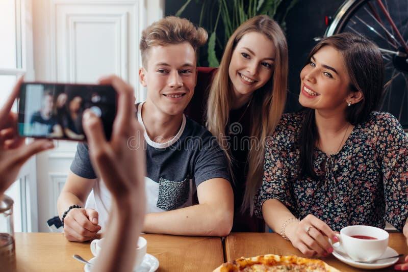 Mãos fêmeas que tomam a foto do grupo de sorriso de amigos que bebem o chá em uma casa acolhedor do café com smartphone foto de stock