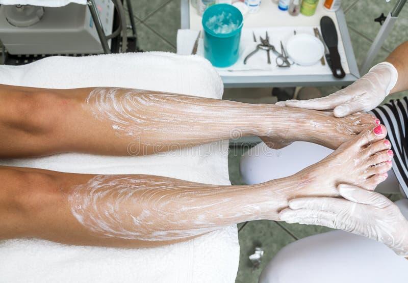 Mãos fêmeas que tratam os pés com o creme hidratando imagens de stock