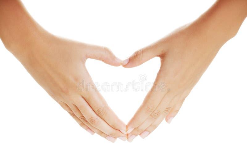 Mãos fêmeas sob a forma do coração foto de stock royalty free