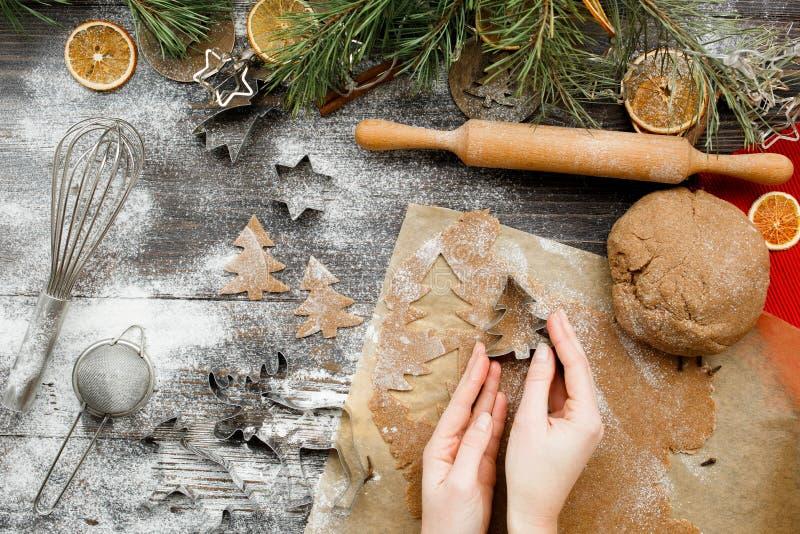 Mãos femininas esculpem figuras de biscoitos de Natal em forma de árvore de natal em uma mesa de madeira de cozinha, vista superi imagens de stock