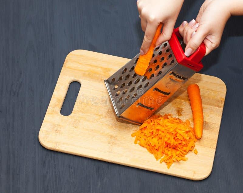 Mãos femininas ralando cenoura em gratê metálico fotografia de stock royalty free