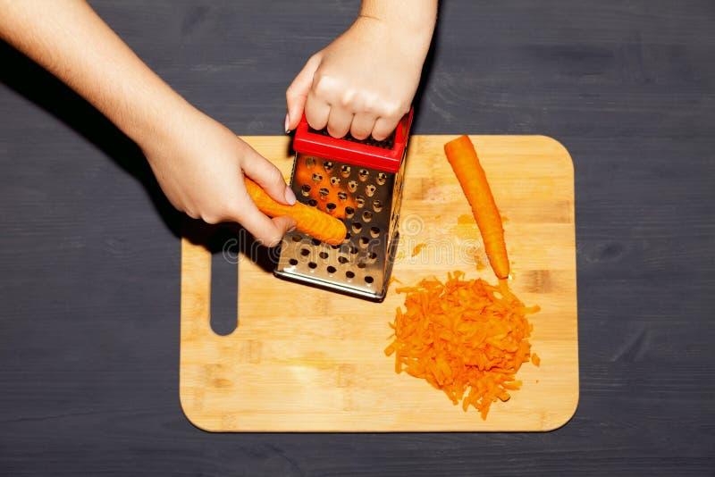 Mãos femininas ralando cenoura em gratê metálico foto de stock