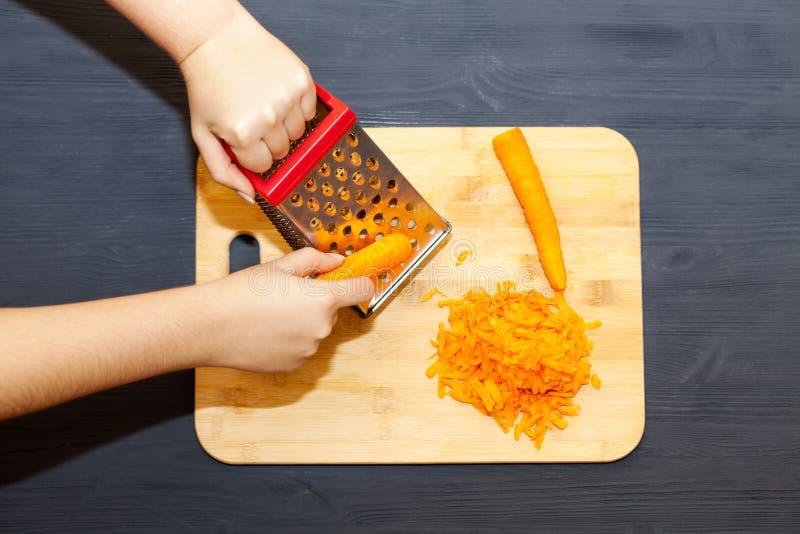 Mãos femininas ralando cenoura em gratê metálico imagens de stock