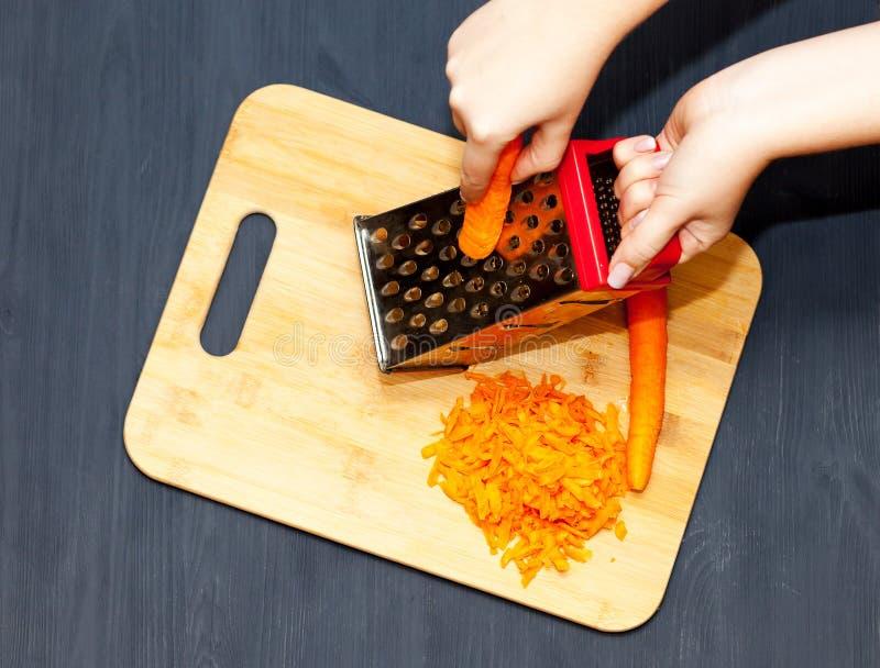 Mãos femininas ralando cenoura em gratê metálico fotos de stock