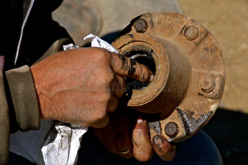 Mãos gordurosas que fixam o rolamento de uma roda e de um exle foto de stock royalty free