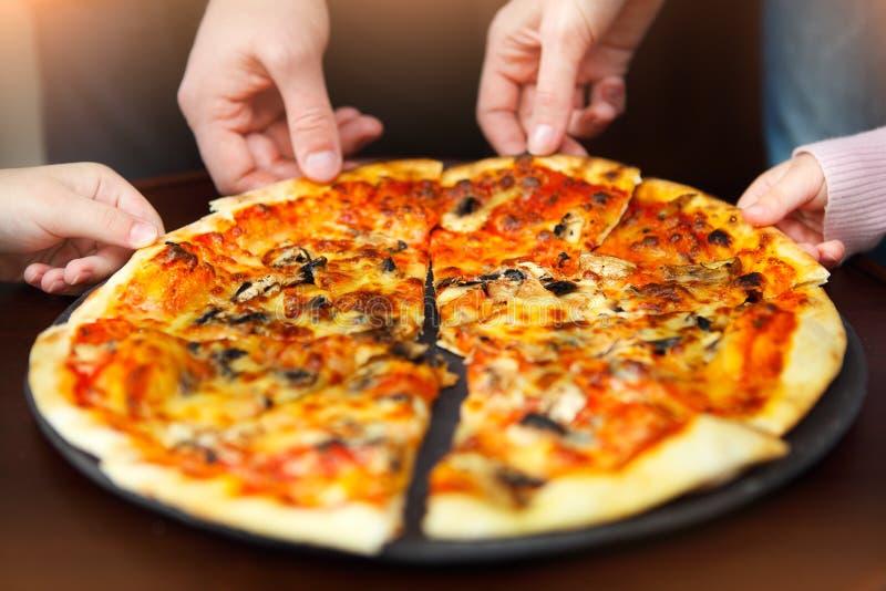 Mãos grandes da família que tomam a pizza da placa fotografia de stock