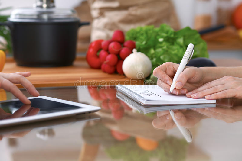 Mãos humanas de duas pessoas fêmeas que usam o touchpad para fazer o menu na cozinha O close up de duas mulheres está fazendo em  imagem de stock royalty free