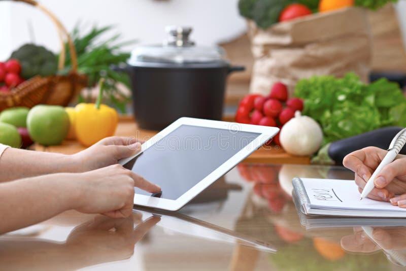 Mãos humanas de duas pessoas fêmeas que usam o touchpad para fazer o menu na cozinha O close up de duas mulheres está fazendo em  fotografia de stock