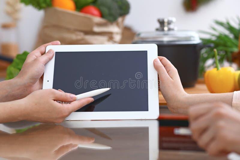 Mãos humanas que apontam na almofada de toque com área de espaço da cópia Mulher dois que faz o menu na cozinha, close up cozimen fotos de stock