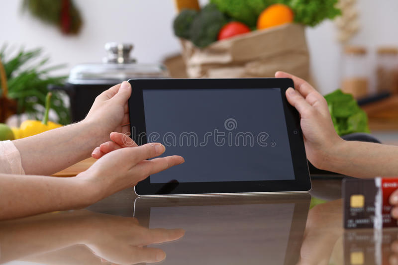 Mãos humanas que apontam na almofada de toque com área de espaço da cópia Mulher dois que faz o menu na cozinha, close up cozimen foto de stock