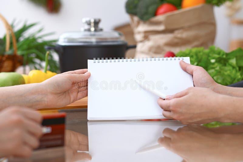 Mãos humanas que apontam no livro de nota com área de espaço da cópia Mulher dois que faz o menu na cozinha, close up cozimento e fotografia de stock