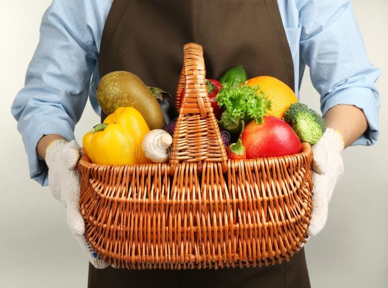 Mãos humanas que guardam a cesta de vime com frutas e legumes diferentes fotografia de stock royalty free
