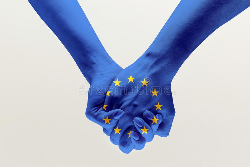 Mãos humanas que guardam coloridas na bandeira azul da UE fotos de stock