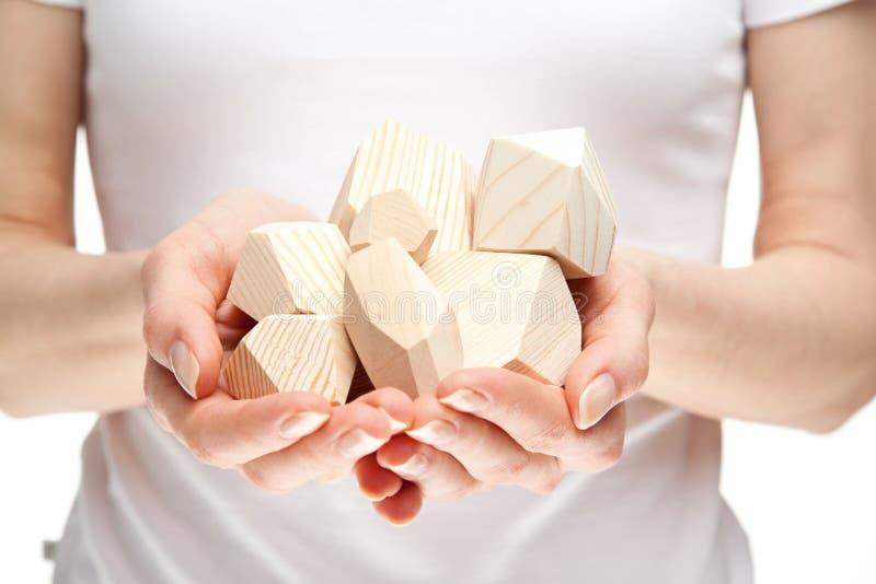 Mãos humanas que prendem o montão de blocos de madeira fotos de stock royalty free