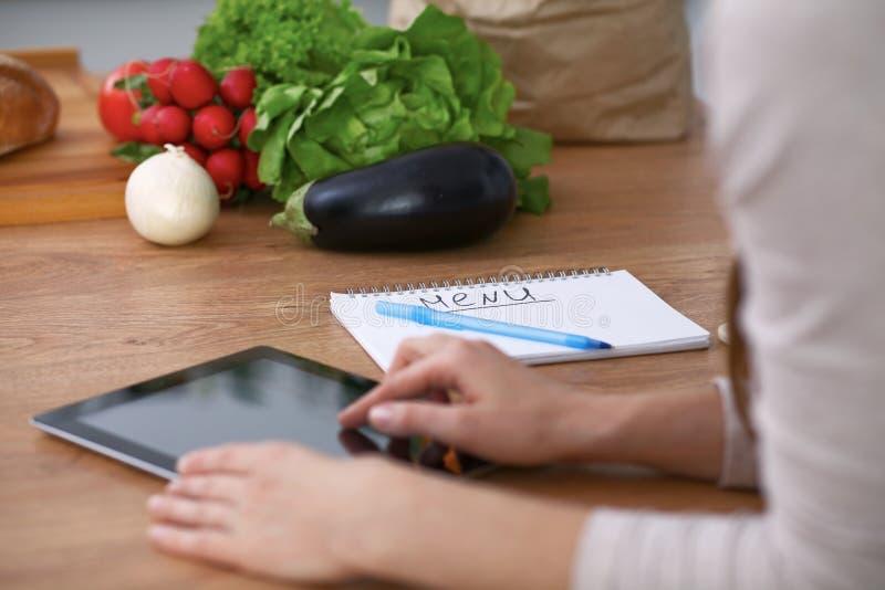 Mãos humanas usando a almofada de toque na cozinha Close up da mulher que faz a compra em linha pelo tablet pc e pelo carro do cr imagens de stock
