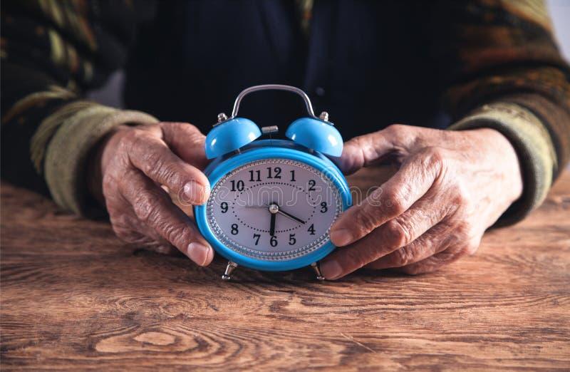 Mãos idosas da mulher com despertador Tempo imagens de stock