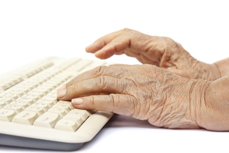 Mãos idosas da mulher no teclado de computador fotos de stock