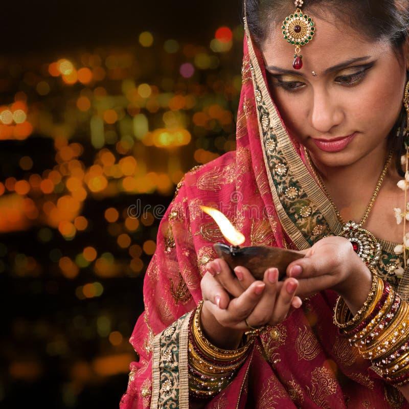 Mãos indianas da menina que guardam a lâmpada de óleo do diwali fotografia de stock royalty free