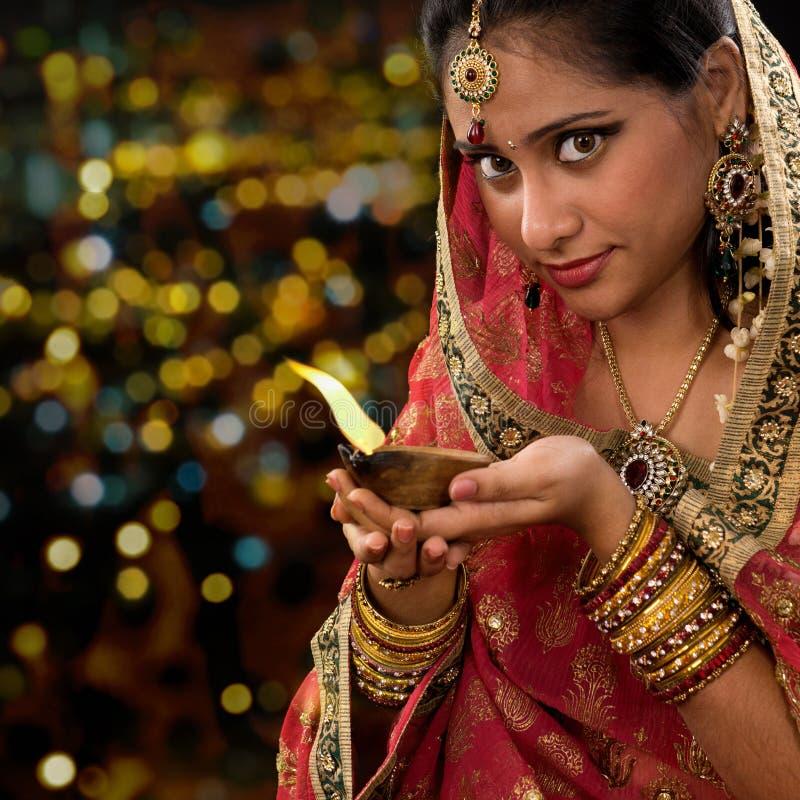 Mãos indianas da mulher que guardam a lâmpada de óleo do diwali foto de stock