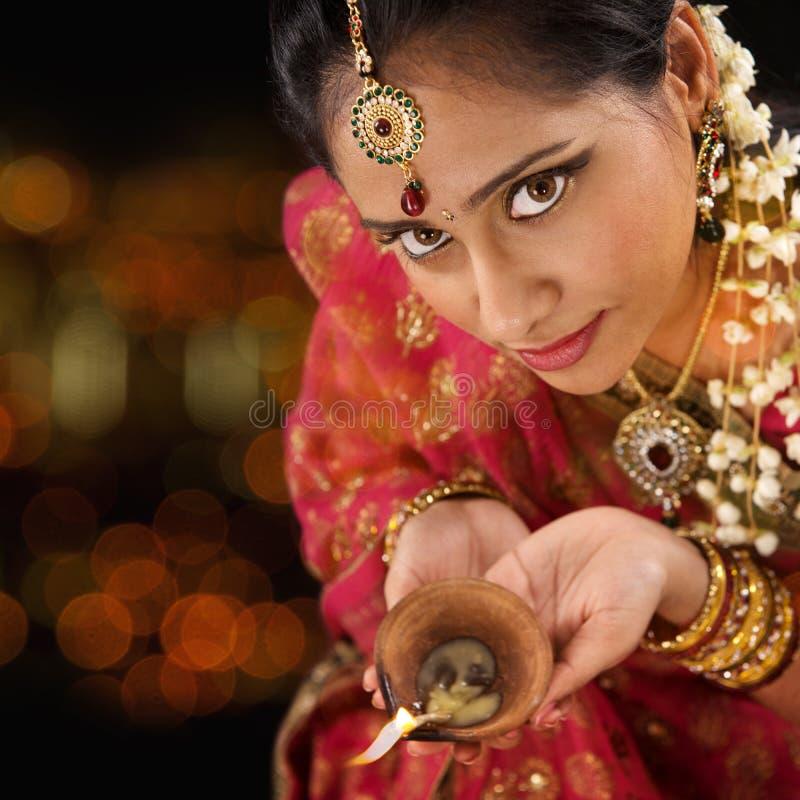 Mãos indianas da mulher que guardam a luz do diwali foto de stock