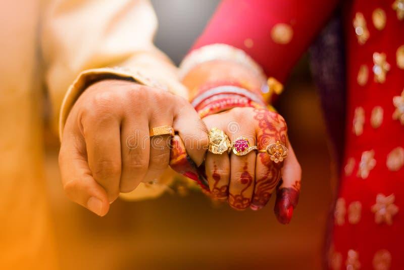 Mãos indianas do noivo da noiva Foco macio, borrão fotografia de stock